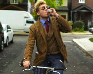 Pat Mills as David Gold rides his bike while drinking alcohol in this still from his movie Guidance