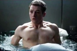 Kingsman movie: a shirtless Taron Egerton wakes up in bed with a pool of rising water surrounding him