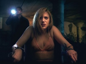 Actress Maike Monroe is tied to a chair in the posters for It Follows horror movie