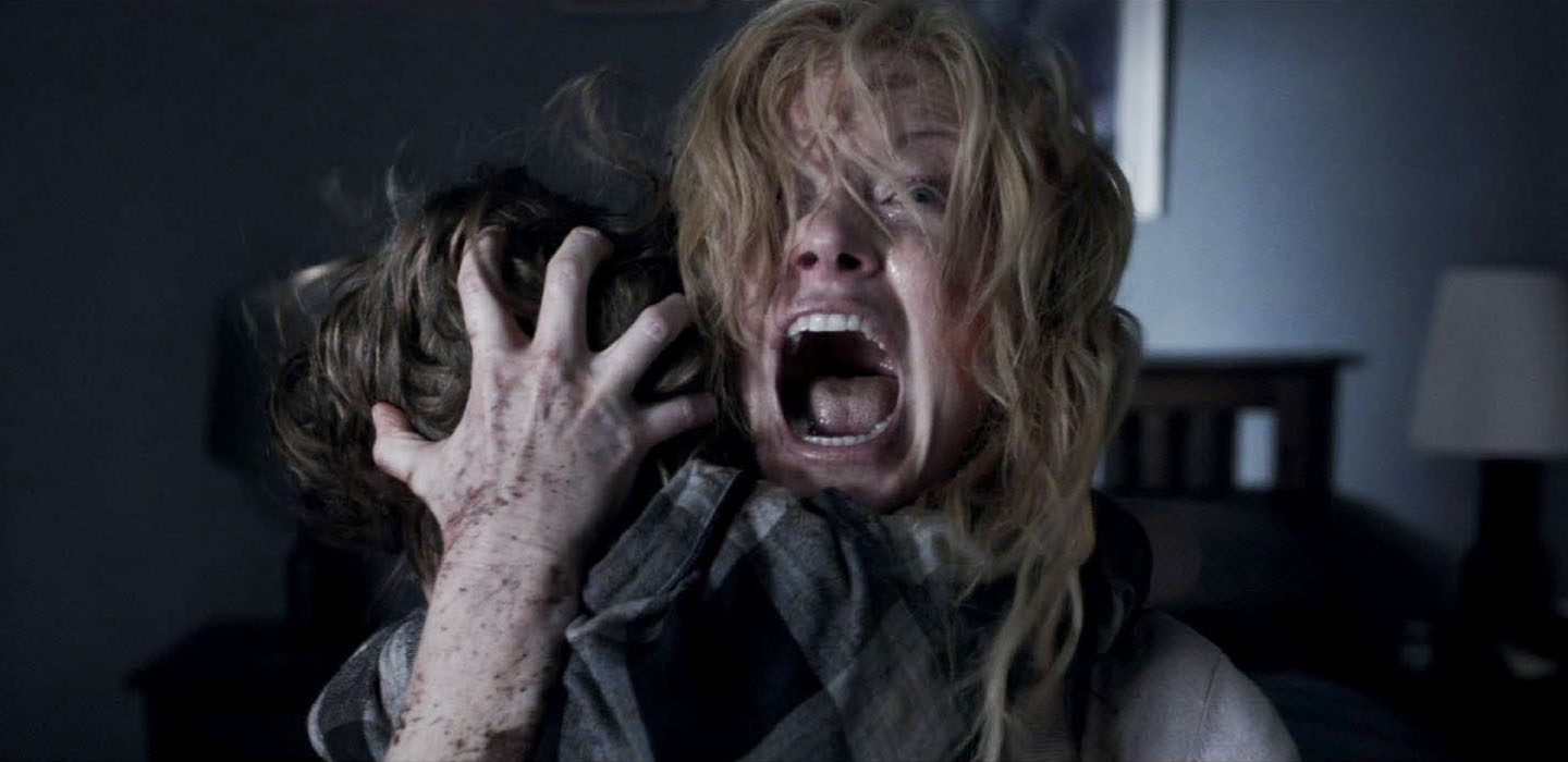 A frightened mother holding her young son close with her hand on the back of his head in The Babadook horror film