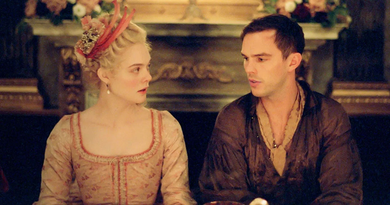 Actress Elle Fanning as Catherine the empress of Russia sitting next to actor Nicholas Hoult as Peter the emperor in a comedic take on Russian history in HULU series, The Great