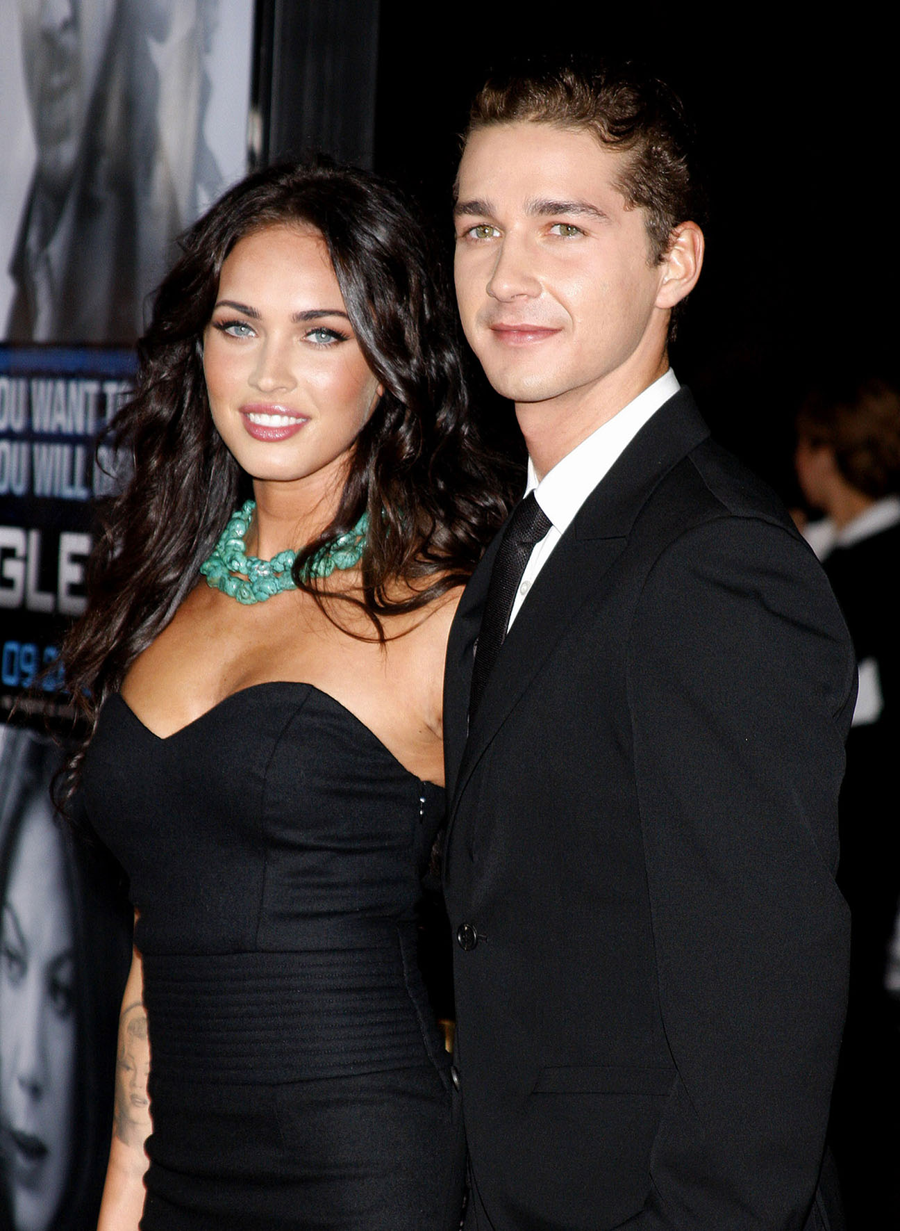 actress Megan Fox poses with co-star, Shia LaBeuf during the premiere of EAGLE EYE movie, both wearing black. Megan wearing a turquoise green necklace.