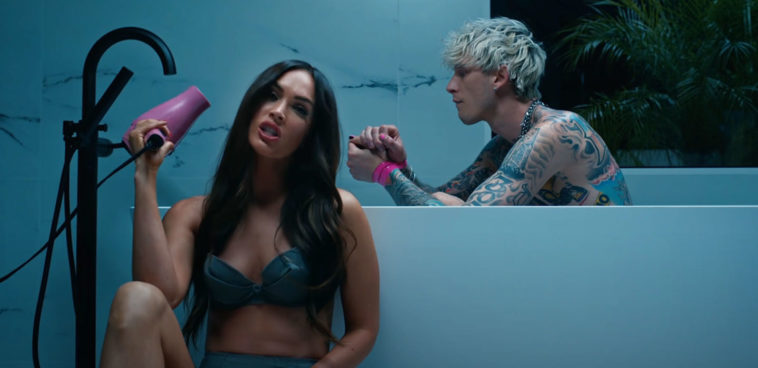 "From music video ""Bloody Valentine,"" actress Megan Fox sits by the bathtub with a blow dryer in hand while rapper Machine Gun Kelly is sitting inside the tub."