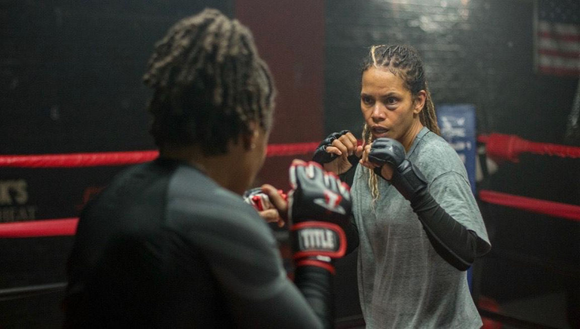Actress Halle Berry is in a boxing ring as MMA fighter, Jackie Justice, wearing dark gray fighting gloves and a black bruise under her left eye. A publicity shot for the movie BRUISED which she has directed.
