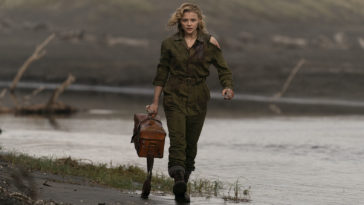 Actress Chloë Grace Moretz as a World War II pilot carries a medicine case walking in the field in this photo from SHADOW IN THE CLOUD film