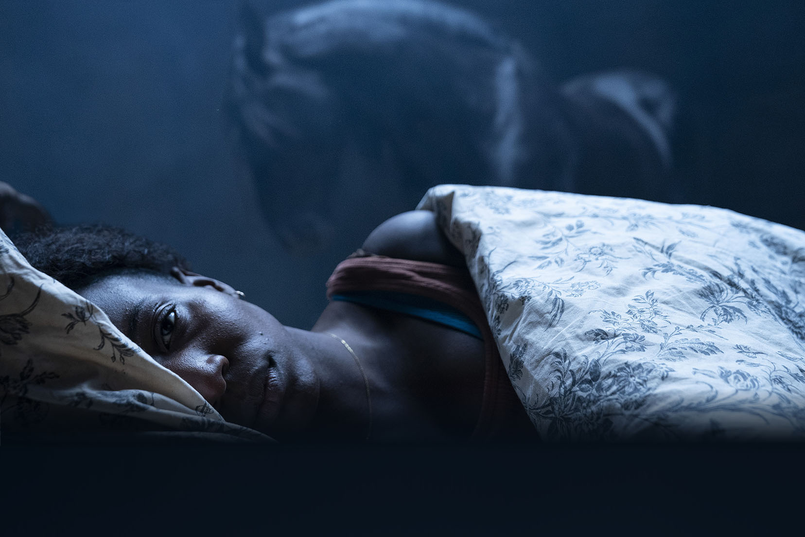 Actress Tamara Lawrence is laying in bed, facing the camera, and looking nervous in horror film, Kindred.