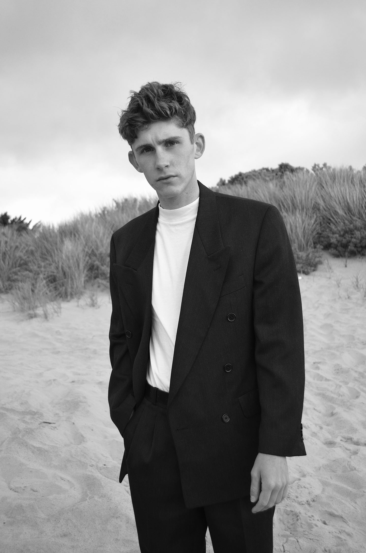 Black and white portrait of Irish actor Fionn O'Shea standing on the stands wearing black suite and trousers - photo by India Mullen