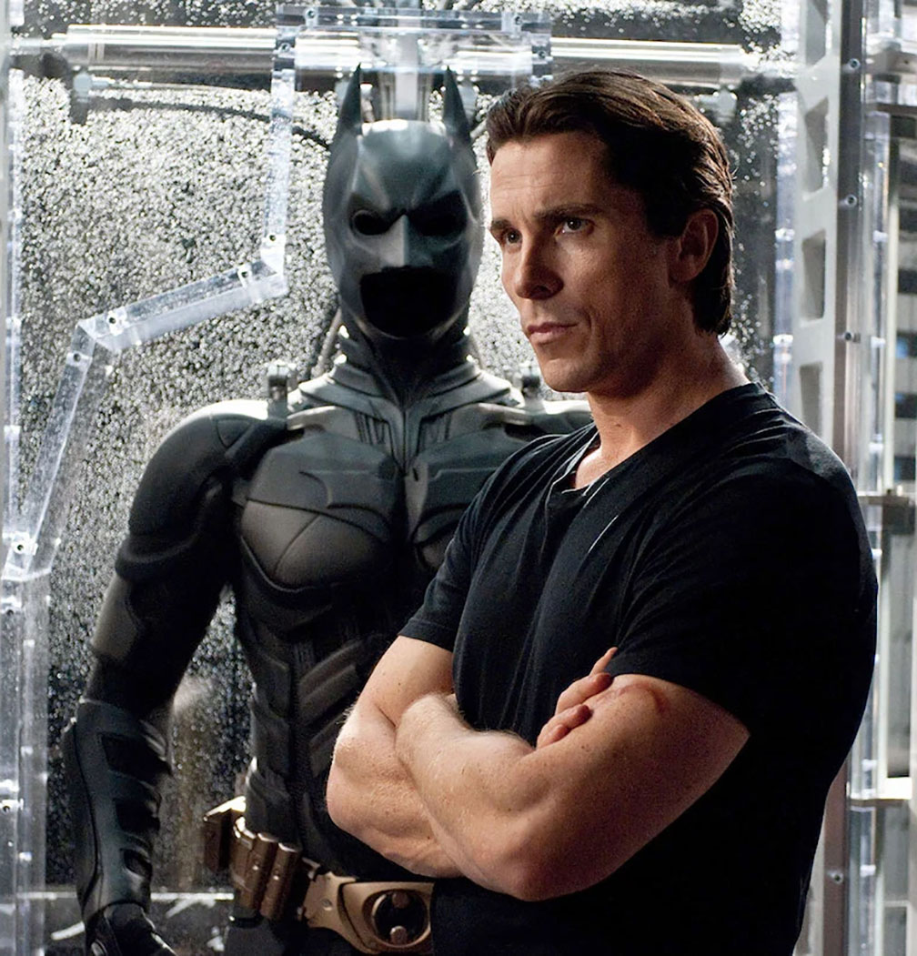 A buff Christian bale stands in front of the Batman costume in The Dark Knight (2008)