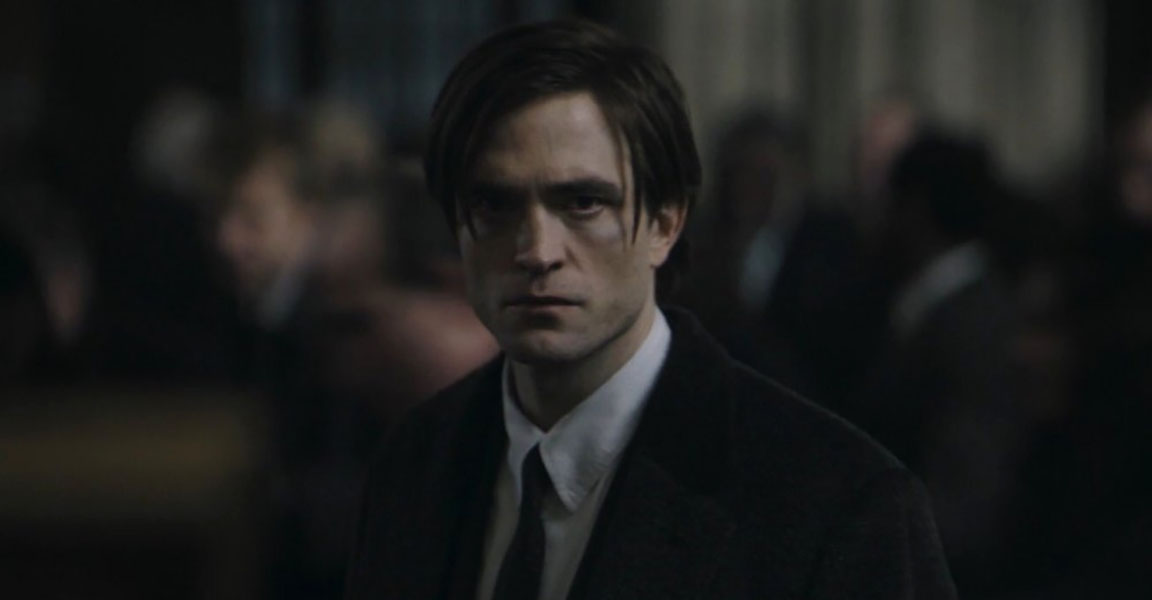 Robert Pattinson in black in a suit and tie in THE BATMAN movie