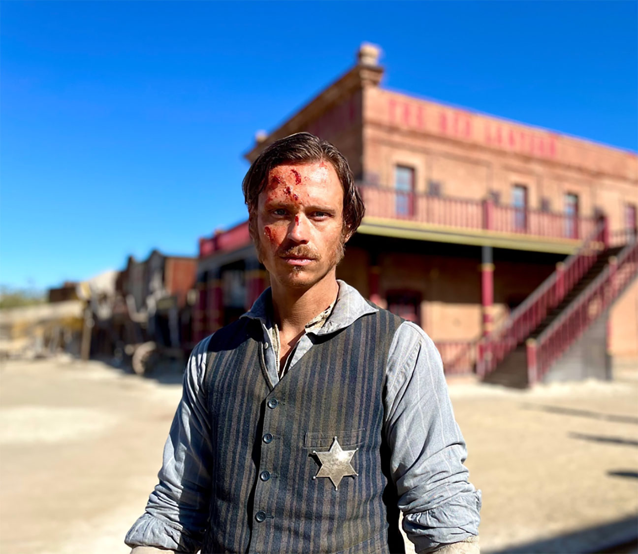 In this photo from the production set, Actor Nicolo Pasetti stanmds in front of an old west building wearing cowboy gear, a tin star on his chest and bruises on his face, on the set of That Dirty Black Bag, upcoming TV series