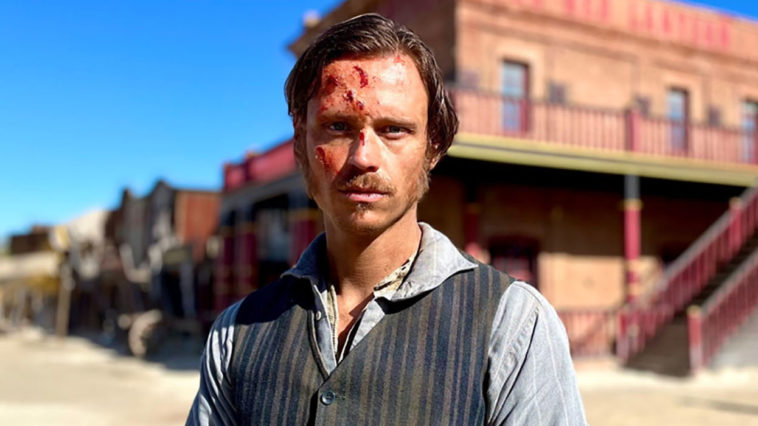 German-Italian actor, Nicolo Pasetti looks bruised in the face as he stands in front of an old building dressed like an old west marshall, wearing a tin star on his chest from the set of That Dirty Black Bag TV series.