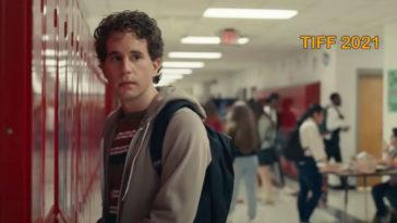 Standing by a row of school lockers. curly haired actor Ben Platt as high school student, Evan Hansen in Dear Evan Hansen movie