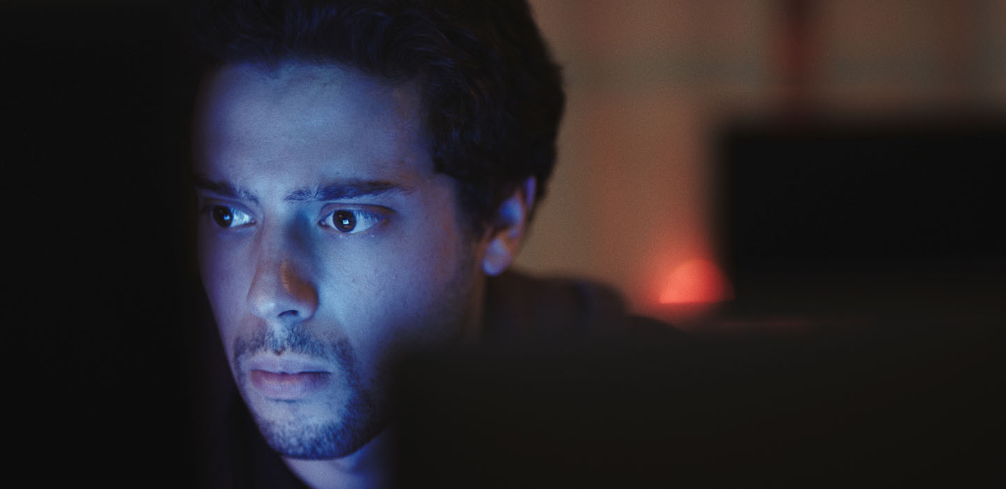 YouTuber turned actor Eric Tabach's face illuminated by what seems to be a computer screen in a still promo photo for DASHCAM, a thriller movie